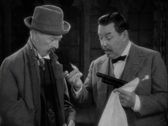 Charlie Chan (Warner Oland) examining the airgun with which an attempt on his life was undertaken in 'Charlie Chan in London' (Forde 1934)