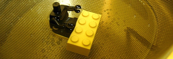 A LEGO minifig being freed from its magnet base